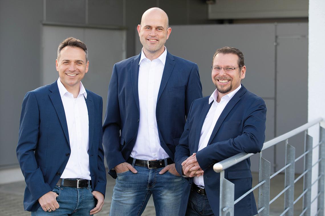 Die drei Geschäftsführer Michael Staggat, Patrik Pintacuda und Wolfgang Klink der PWM Technology Group vor dem Eingang in das Firmengebäude in Bodnegg